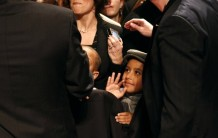 Child waves as Obama passes before him at DCCC rally in Providence