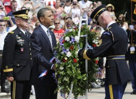 A soldier helps Obama lay a Memorial Day wreath at the Tomb of the Unknowns at Arlington Cemetery in Arlington, Virginia