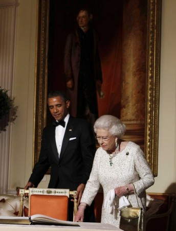 U.S. President Barack Obama walks with Queen Elizabeth to sign the guest book inside Winfield House in London