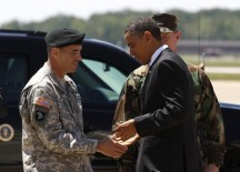 U.S. President Barack Obama gives a challenge coin to Brigadier General Jeffrey Colt as he arrives to speak to troops at Fort Campbell in Kentucky