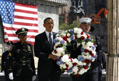 Obama carries a wreath accompanied by a police officer and a firefighter as he arrives to place the wreath at the Ground Zero site during a visit to the World Trade Center site in New York