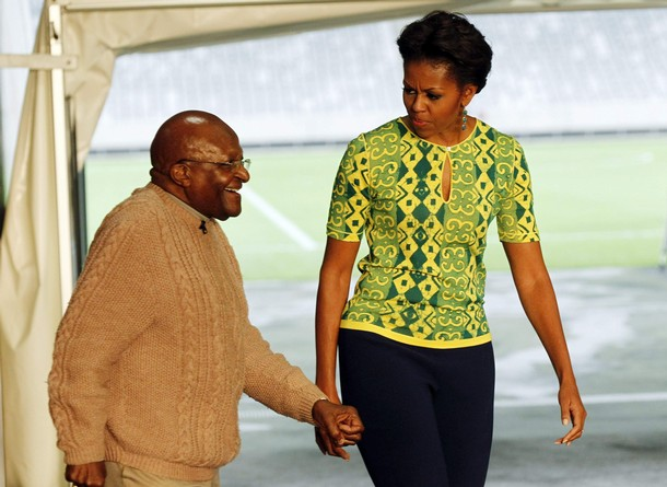 Archbishop Desmond Tutu walks with U.S. first lady Michelle Obama during a visit to Cape Town stadium