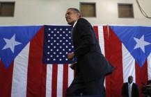 U.S. President Barack Obama walks before he speaks inside hanger at Luis Munoz Marin International Airport in Puerto Rico