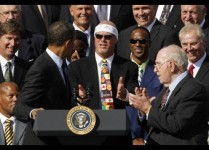U.S. President Barack Obama looks at Jim McMahon alongside Defensive Co-Ordinator Buddy Ryan at the White House in Washington