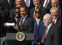 U.S. President Barack Obama looks at Jim McMahon alongside Defensive Co-Ordinator Buddy Ryan at the White House in Washington
