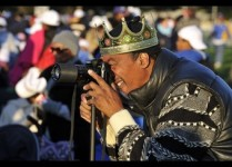 A man wearing a crown takes pictures at