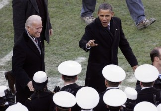 Biden and Obama greet white-hatted U.S. Naval Academy midshipment as they walk on the field prior to the 112th Army-Navy football game in Landover, Maryland