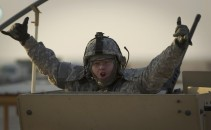 A United States soldier gestures as he crosses the Iraqi border into Kuwait