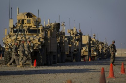 Soldiers from the 3rd Brigade Combat Team, 1st Cavalry Division walk past a line of MRAP vehicles while waiting at a staging area in Camp Adder to be part of the last U.S. military convoy to leave the country near Nasiriyah