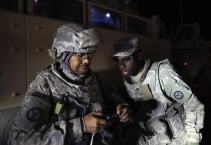 Sergeant Kilwe MuDiwa and Specialist Jamaal Little John from the 3rd Brigade Combat Team, 1st Cavalry Division look at a photograph of themselves outside of a MRAP vehicle before departing Camp Adder as part of the last U.S. military convoy to leave Iraq
