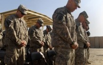 Soldiers from the 3rd Brigade, 1st Cavalry Division bow their heads in prayer while preparing to depart from Iraq at Camp Adder, now known as Imam Ali Base, near Nasiriyah, Iraq
