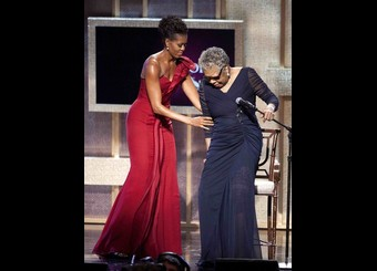 First Lady Michelle Obama assists honouree Maya Angelou at the BET Honors in Washington
