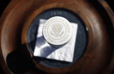 A glass of water on stage for U.S. President Barack Obama features a paper cover with the presidential seal during an event at a UPS facility in Las Vegas