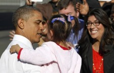 U.S. President Barack Obama speaks with a young girl at a UPS facility in Las