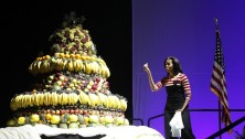 "U.S. First Lady Michelle Obama looks at a huge birthday cake made of fruits during an event to promote her ""Let's Move"" initiative in Des Moines"