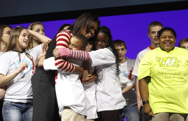 "U.S. First Lady Michelle Obama hugs children after they danced together to promote her ""Let's Move"" initiative in Des Moines"