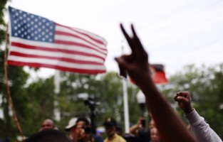 Demonstrators hold their hands aloft during a march and rally to the front of the Sanford Police Department for Trayvon Martin in Sanford, Florida
