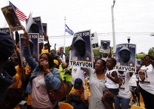 Demonstrators hold signs aloft during a march and rally to the front of the Sanford Police Department for Trayvon Martin in Sanford, Florida