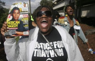 Wearing a hoodie, Stevenson holds up a magazine as she participates in a march organized by the National Christian League of Councils for slain teen Trayvon Martin in Tallahassee