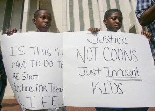 Two young boys hold signs during a rally organized by the National Christian League of Councils for slain teen Martin in Tallahassee