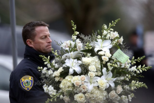 A police officer carries flowers into a funeral service for 6-year-old Noah Pozner, Monday, Dec. 17, 2012