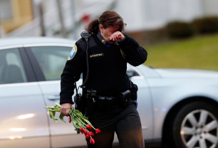 Newtown police officer Maryhelen McCarthy weeps as she brings flowers to a memorial