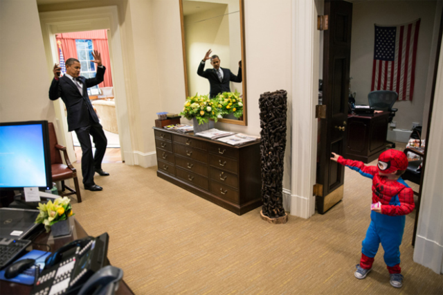 President Obama pretends to be caught in Spider-Man's web while greeting a White House staffer's son.