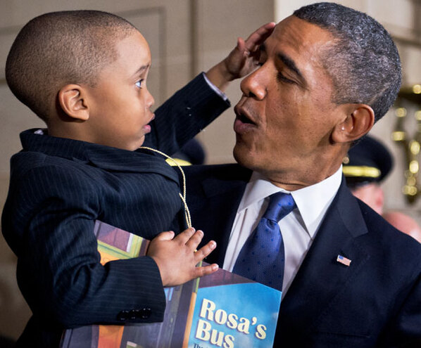President Obama with a three-year-old relative of Rosa Parks after the unveiling of a statue in her honor