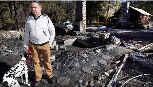 Rick Heltebrake with his dog Suni looks over the burned-out cabin where Christopher Dorner's remains were found after a police standoff Tuesday near Big Bear, Calif. Friday Feb. 15 2013. AP Photo-Nick Ut