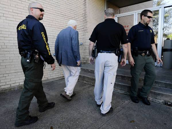 Kaufman County, Texas, law enforcement officials escort an employee into the courthouse. Security remained tight across the state after a second prosecutor was slain.