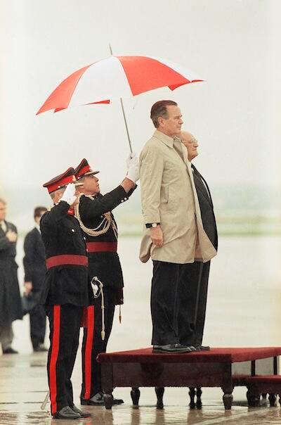 Bush with Marines holding umbrella