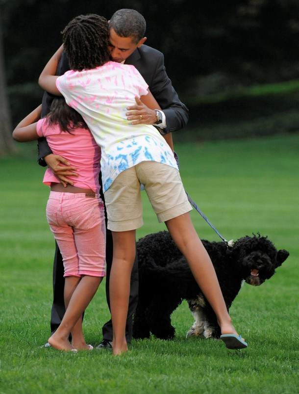 President Obama is welcomed back to the White House by his daughters and their dog