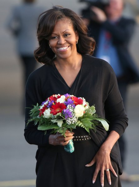 Michelle Obama, wife of US President Barack Obama , carries a bouquet of flowers upon her arrival at Tegel Airport in Berlin, Germany, 18 June 2013. Photo: Kay Nietfeld/dpa +++(c) dpa - Bildfunk+++