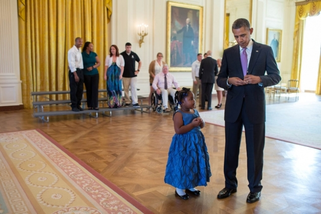 President Barack Obama writes a school excuse note for Alanah Poullard, 5, while visiting with Wounded Warriors and their families in the East Room