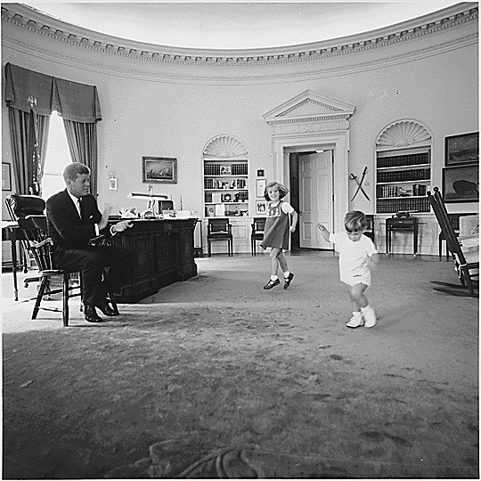 President John F. Kennedy watches Caroline Kennedy and John F. Kennedy Jr. play in the Oval Office