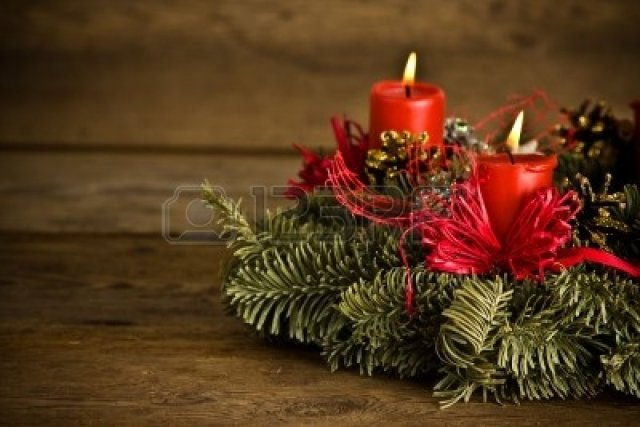 6266588-green-christmas-wreath-decorated-with-red-burning-candles-red-ribbons-and-golden-pine-cones-on-timbe