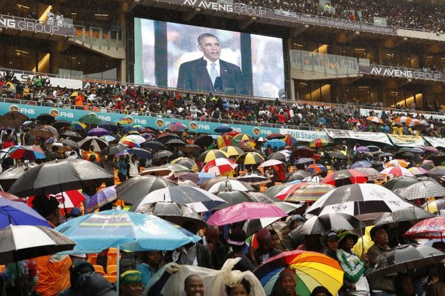 Barack Obama speaking in the background over a sea of umbrellas.