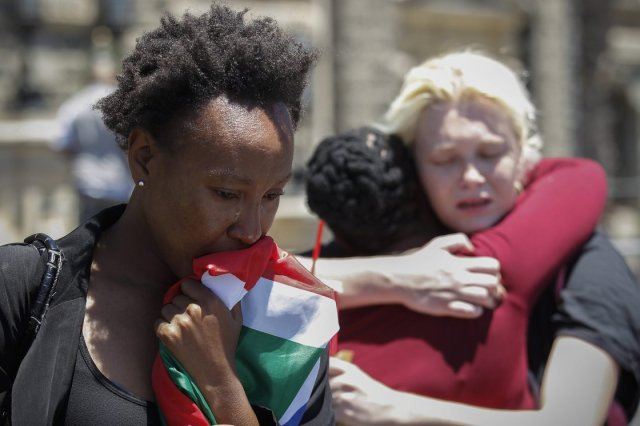 Mandela Mourning- Mourners weep and embrace in front of Cape Town City Hall