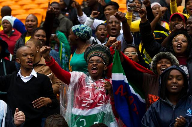 People sing and dance as they arrive at Nelson Mandela's memorial