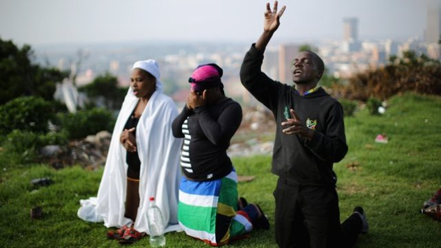 People worship on a hill overlooking Johannesburg as they remember and mourn Nelson Mandela1
