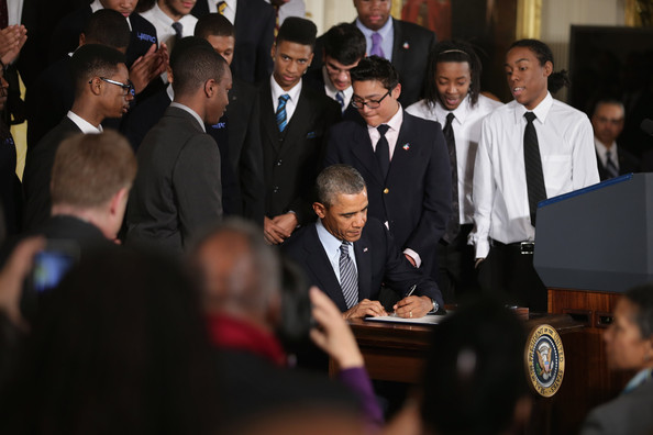 Barack Obama signs an executive memorandum related to his My Brother's Keeper initiative in the East Room at the White House February 27, 2014