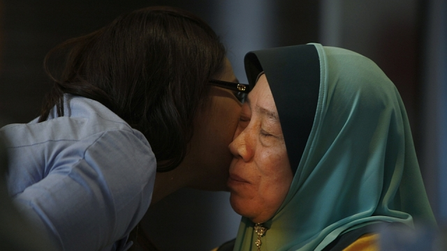 A journalist kisses Wan Tom Wan Chik, the mother of 33 year old Malaysia Airlines flight MH370 passenger Mohd Sofuan Razak after interview.
