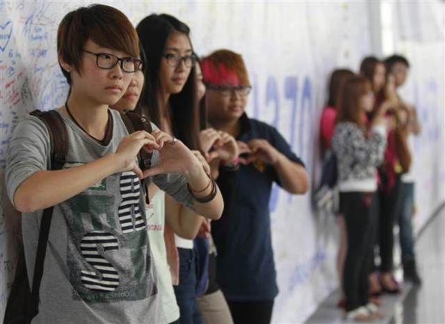 Well-wishers pose for pictures next to messages written about the missing Malaysian Airline plane at Kuala Lumpur International Airport.