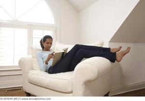 Black woman reading book in armchair