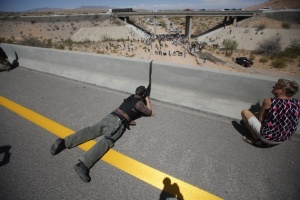 Tea Party racist-Eric Parker, who lives in central Idaho, aims his weapon from a bridge as protesters gather by the Bureau of Land Management's base camp in Bunkerville, Nevada. (Jim Urquhart-Reuters)