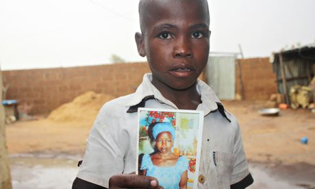 A boy holds up a photo of his 19-year-old sister, one of the schoolgirls kidnapped by Boko Haram