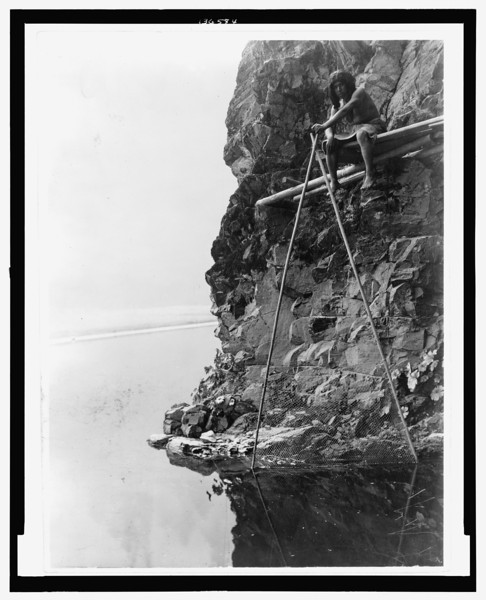 Edward S Curtis Collection- Photograph shows a Hupa man sitting on a platform on a rocky cliff, handling a fishing net.