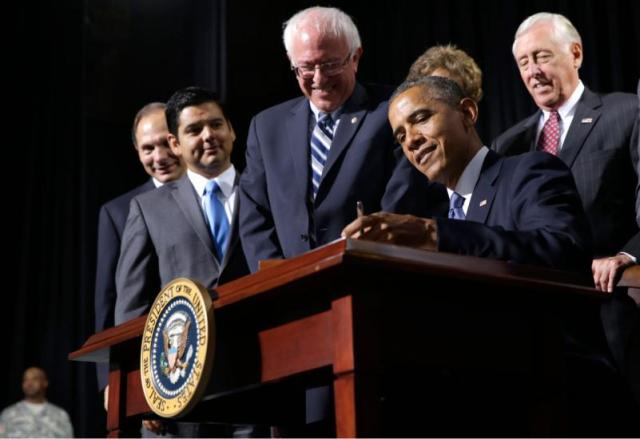 Barack Obama, flanked by Senate Veterans Affairs Committee Chairman Sen. Bernie Sanders, I-Vt., left, and House Minority Whip Steny Hoyer of Md., right, signs H.R. 3230, the Veterans' Access to Care