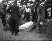 Family and community members lower the casket of a victim into a grave, July 28, 1946