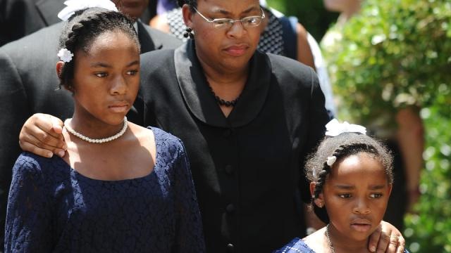 Sen. Clementa Pinckney's wife Jennifer Pinckney, center, and her daughters, Eliana, left, and Malana, right, follow his casket into the South Carolina Statehouse, Wednesday, June 24, 2015, in Columbia, S.C. Pinckney's open coffin was being put on display under the dome where he served the state for nearly 20 years. Pinckney was one of those killed in a mass shooting at the Emanuel AME Church in Charleston. (AP Photo/Rainier Ehrhardt)
